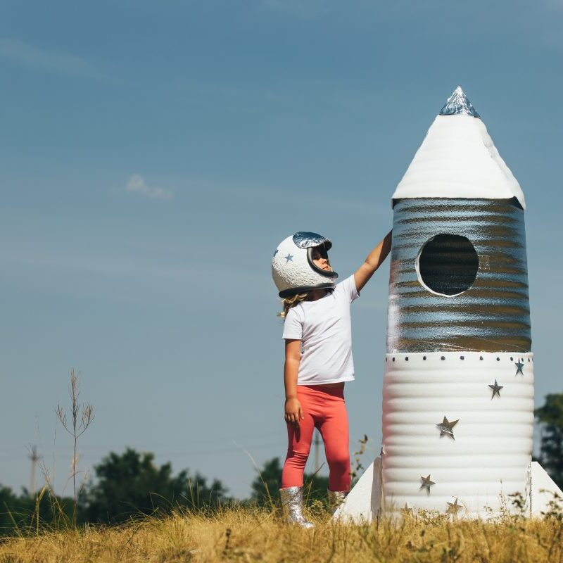 Happy child girl dressed in an astronaut costume playing with hand made rocket. Summer outdoor.